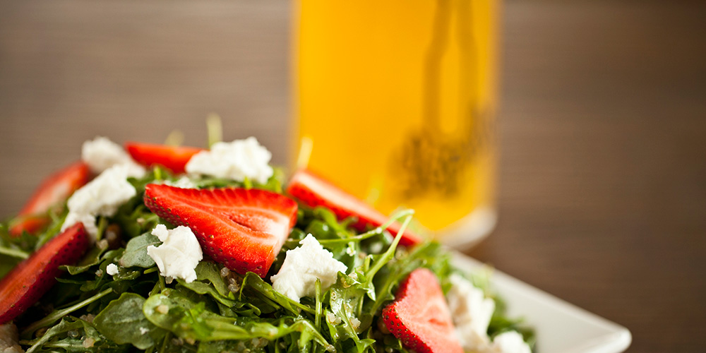 Our refreshing Arugula Salad with a pint of craft beer in the background