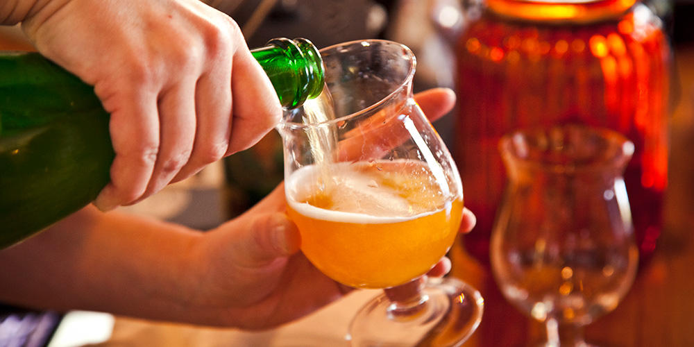 Close-up of a patron at Lupulo pouring a glass of Cantillon sour ale that they purchased from our extensive cellar list