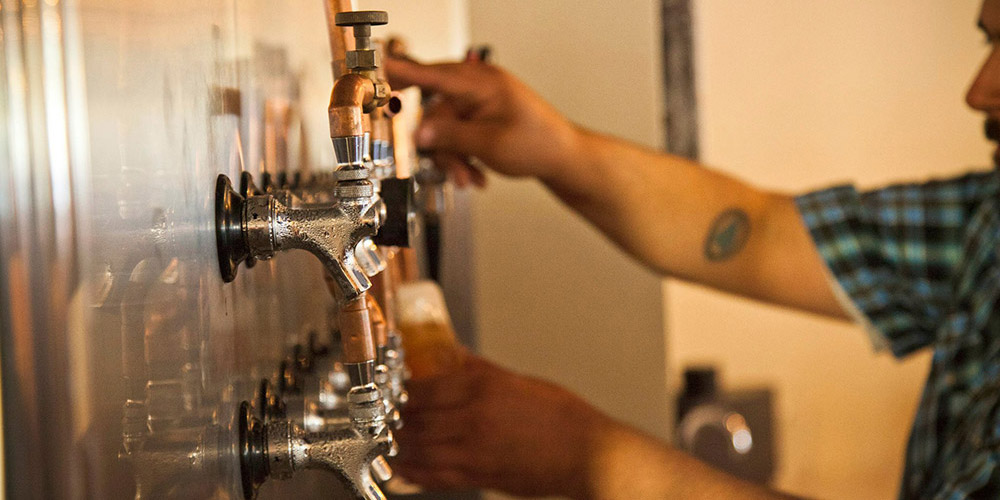 One of Lupulo's talented beertenders pouring a pint of craft beer from the tap wall