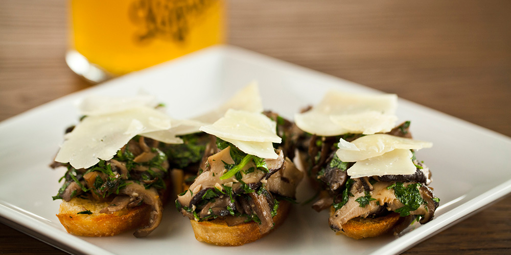 Our delicious Montaditos de hongos, or mushroom and manchego cheese toast, with a cold pint of craft beer in the background