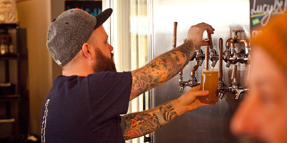 Yet another highly-skilled beertender pouring a pint of craft beer from Lupulo's wall of taps