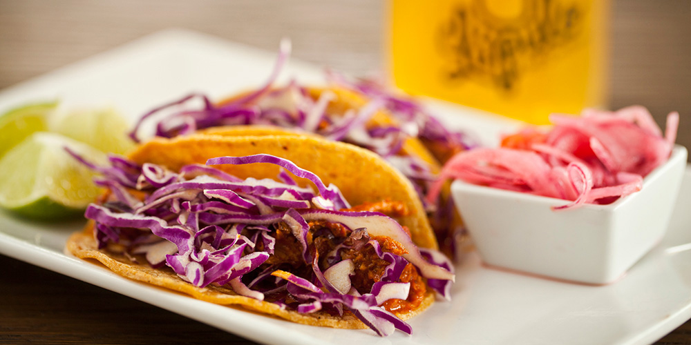 Tacos de Pibil, or orange and achiote braised pork tacos, with pickled onions and limes on the side, and a shimmering pint of cold craft beer in the background